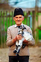 Senior farmer holding a baby goat outdoor