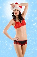 young beautiful girl wearing sexy lingerie and a christmas hat posing over white background