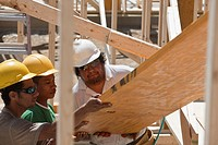 Carpenters lifting a laminated beam at a construction site