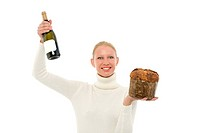 portrait of a young caucasian woman wearing a white turtleneck sweater and holding a panettone and a bottle of champagne