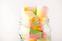 Soft, fluffy, colorful marshmallow in a glass jar on a white background