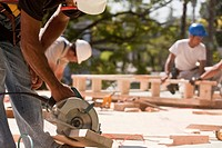Carpenters using circular saw at a construction site with gable frame in the background
