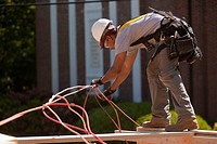 Carpenter untangling power cord at a construction site