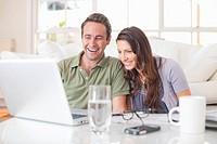 Hispanic couple using laptop together