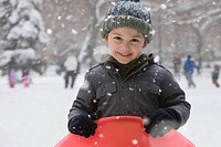 Caucasian boy sledding in snow