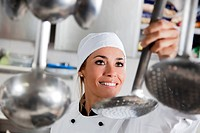 mid adult female chef taking kitchen utensil