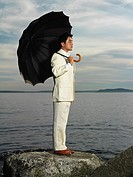 Japanese businessman holding umbrella near ocean