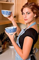 Pretty young woman prepares dinner in her kitchen