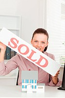 A businesswoman is holding a sold sign above a miniature house