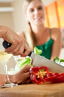 Man slices a red pepper on a cutting board as a woman looks on.