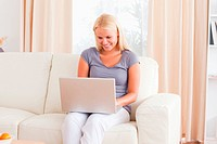 Happy woman using a laptop in her living room