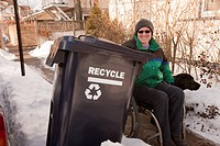 Woman with multiple sclerosis doing recycling with a service dog