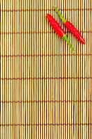 Two red chilli at the right corner of a bamboo mat, empty left space for text
