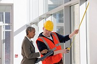 Construction engineer with an architect measuring commercial windows