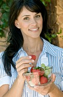 happy smiling beautiful brunette enjoying a bowl of fruit outside on her patio, grapes and strawberries