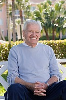 Portrait of a man sitting on a park bench and smiling