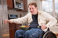 Man with spinal cord injury in a wheelchair getting bowl of fresh fruits from refrigerator