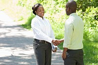 Two businesspeople are standing in a park and shaking hands.