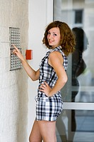 Young woman is using a house intercom