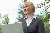 Woman smiles as she uses a laptop outdoors.