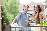 Man and woman smile from an outdoor patio.