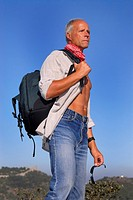 Handsome mature man adventurer posing outdoors with a backpack