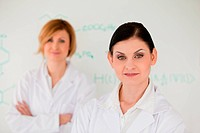 Two cute women in front of a white board in a lab