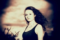 Girl, 14 years, with long hair in front of a gloomy cloudy sky, portrait