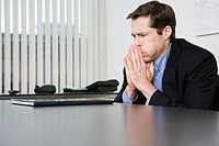 View of a contemplative businessman sitting in an office