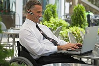 Businessman sitting in a wheelchair and using a laptop
