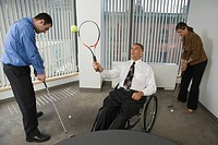 Man and a woman playing golf with a handicapped businessman playing tennis in a wheelchair