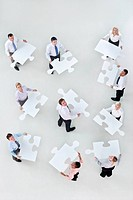 Portrait of business people holding large jigsaw pieces
