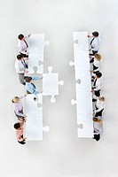 Business people standing face to face in rows and holding large jigsaw pieces