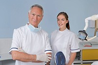 Portrait of smiling dentist and dental assistant in dentist's office