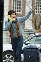 Young woman talking on a pay phone and waving her hand