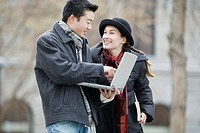 Side profile of a young man using a laptop and a young woman looking at her