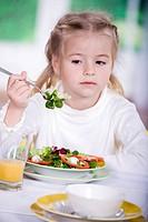 young girl eating salad at home. A studio shoot.