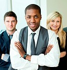 Afro_American businessman with folded arms with his colleagues smiling at the camera