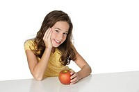 Cute Caucasian girl happy about eating an apple