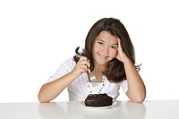 Cute Caucasian child eating a slice of chocolate cake