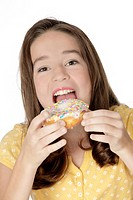Cute Caucasian girl eating a donut on a white background