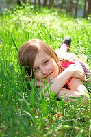 Cute little girl is lying on green meadow
