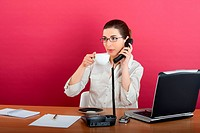 Portrait of a young business woman speaking on the phone and drinking a coffee