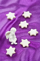 Cinnamon stars and an angel figurine on a purple surface