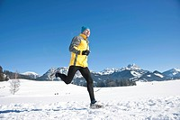 Man jogging in the snow in the mountains