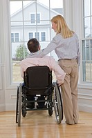 Man sitting in a wheelchair with a woman standing beside him