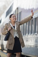 Hispanic woman waving goodbye at a railroad station platform