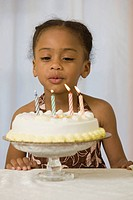 Hispanic girl blowing out candles on a cake