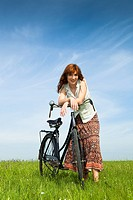 Happy young woman on a green meadow with a vintage bicycle