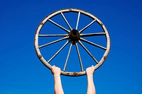 hands holding an old wooden wheel against blue sky